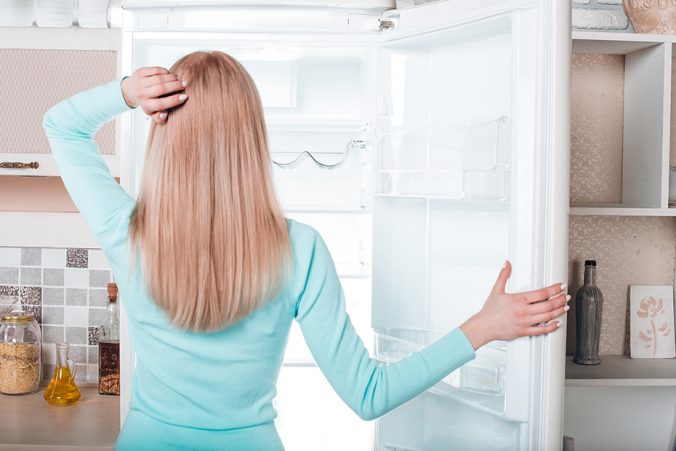 A person standing in front of a refrigerator