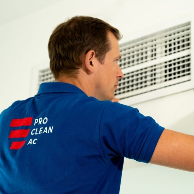 A member of the Pro Clean AC team removing an AC grille to clean it