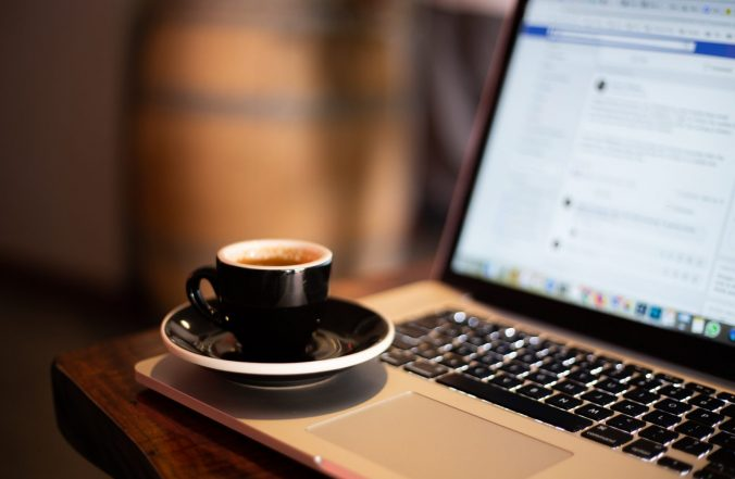 A cup of coffee and a laptop computer sitting on top of a table