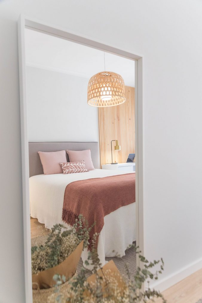 A bedroom with a large mirror